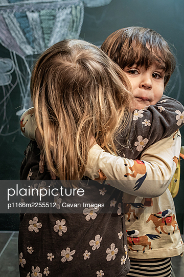 Children hug each other in class affectionately with a blackboard in t - p1166m2255512 by Cavan Images