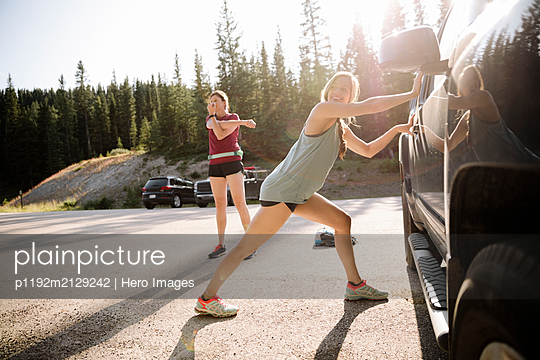 Female runners stretching, preparing in sunny parking lot - p1192m2129242 by Hero Images