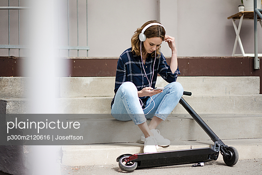 Young womanwith electric scooter, sitting on stairs, listening music - p300m2120616 by Joseffson