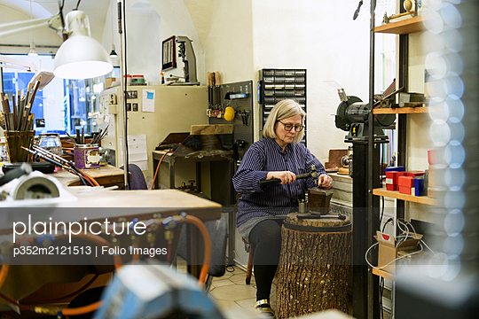 Goldsmith working at anvil - p352m2121513 by Folio Images