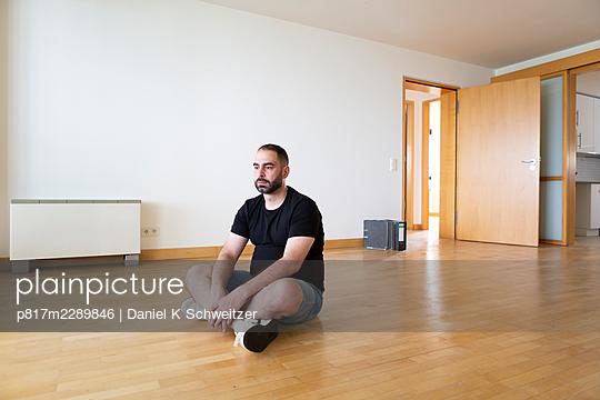 Man with full beard sitting in empty apartment - p817m2289846 by Daniel K Schweitzer