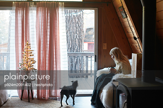 Woman drinking on sofa with dog at home - p924m2091402 by heshphoto