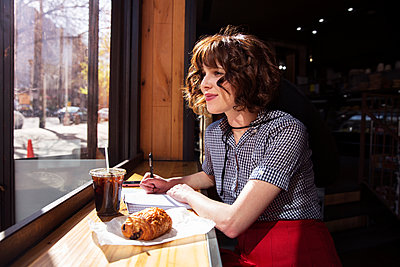 Woman looking through window while sitting in cafe - p1166m1485621 by Cavan Images
