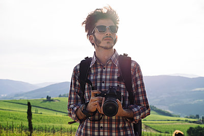 Thoughtful young man holding digital camera while standing against hills and clear sky - p1166m1542287 by Cavan Social