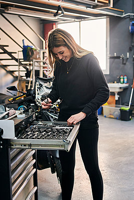 A happiness woman is working in a mechanic shop - p1166m2268339 by Cavan Images
