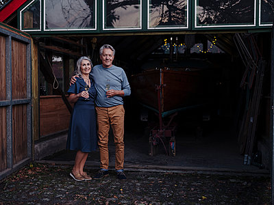 Senior couple standing in front of boathouse with glass of champagne - p300m2154972 von Gustafsson
