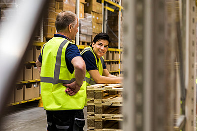 Smiling young worker looking at senior coworker standing at distribution warehouse - p426m2018837 by Maskot