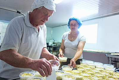 Cheesemakers preparing rows of fresh cheese - p429m2019515 by Seb Oliver