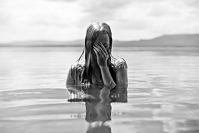 Caucasian teenage girl covering her face in lake - p555m1415076 by Vladimir Serov