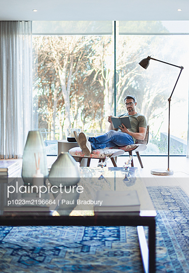 Man relaxing with feet up, reading book in living room - p1023m2196664 by Paul Bradbury