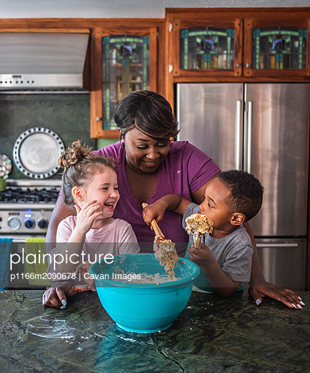 Mother smiling while kids make cookies together - p1166m2090678 by Cavan Images