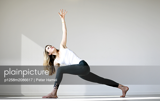 Young woman doing yoga - p1258m2086617 by Peter Hamel