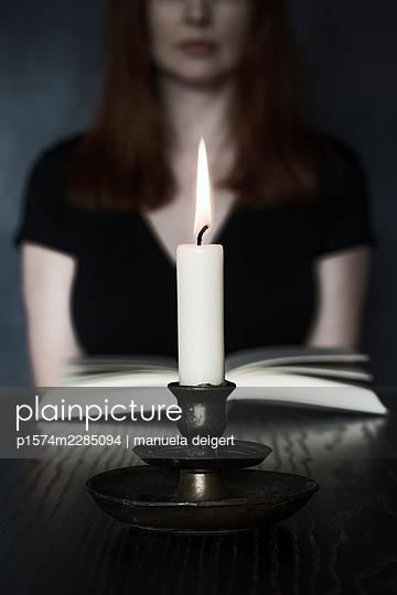 Woman reading by candlelight - p1574m2285094 by manuela deigert