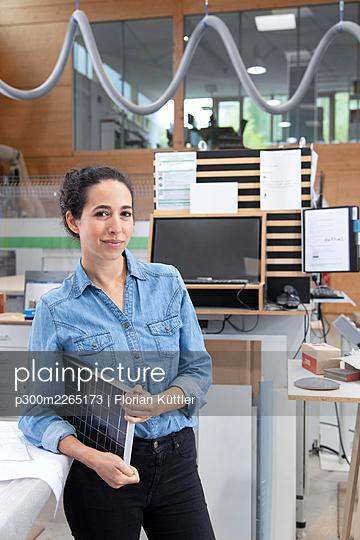Female entrepreneur with solar panel model standing in factory - p300m2265173 by Florian Küttler