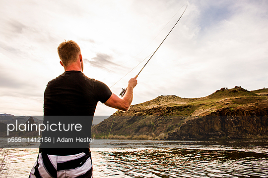 Caucasian man fishing in remote lake - p555m1412156 by Adam Hester