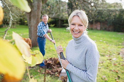Portrait smiling, confident mature woman raking autumn leaves in backyard - p1023m2010396 by Sam Edwards