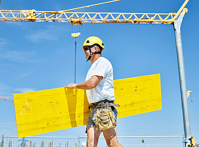 Construction worker carrying plywood construction site - p300m1588049 by Christian Vorhofer