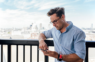 UK, London, man using cell phone on a roof terrace - p300m2062082 by Marco Govel