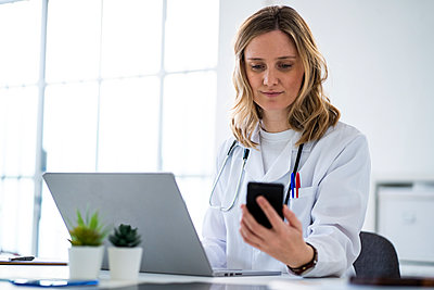 Blond female doctor using mobile phone sitting at desk in medical clinic - p300m2265394 by Giorgio Fochesato