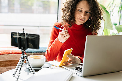 Female influencer with laptop looking in smart phone at cafe - p300m2282181 by COROIMAGE