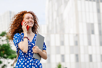 Smiling young woman holding laptop while talking on smart phone in city - p300m2300113 by COROIMAGE
