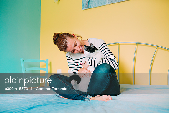 Happy woman with a black and white cat on the bed - p300m1587014 von Gemma Ferrando