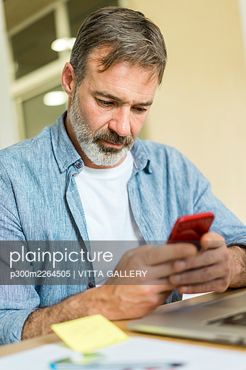 Male entrepreneur using smart phone in office - p300m2264505 by VITTA GALLERY
