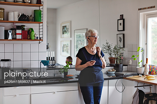 Retired senior woman holding smart phone while listening to in-ear headphones in kitchen at home - p426m1569837 by Maskot