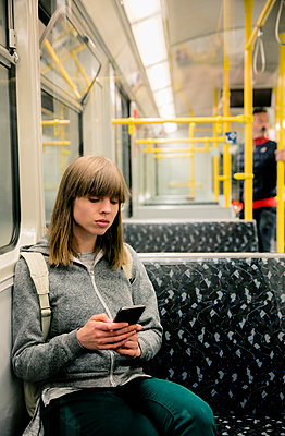 Junge Frau mit Rucksack sitzt in der U-Bahn - Mann im Hintergrund - p1212m1137020 von harry + lidy
