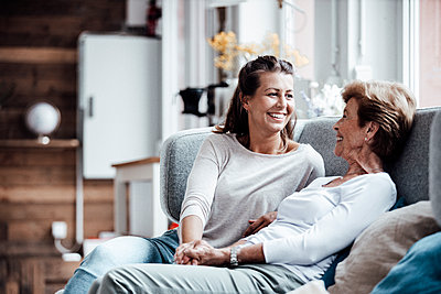 Smiling beautiful woman holding grandmother's hand while sitting on sofa a home - p300m2276868 by Gustafsson