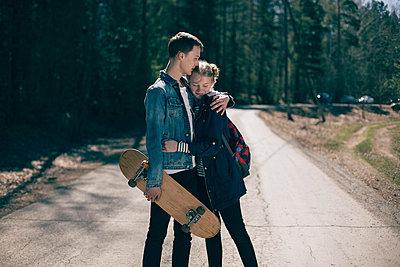 Caucasian couple with skateboard hugging in road - p555m1531606 by Vladimir Serov