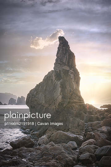 Nice sunset over the ocean behind a rock formation - p1166m2191918 by Cavan Images