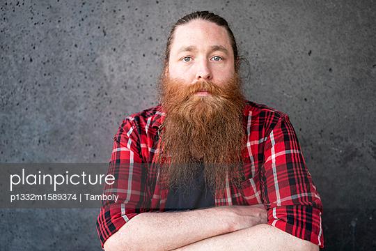 Porträt eines männlichen Hipsters mit verschränkten Armen - p1332m1589374 von Tamboly