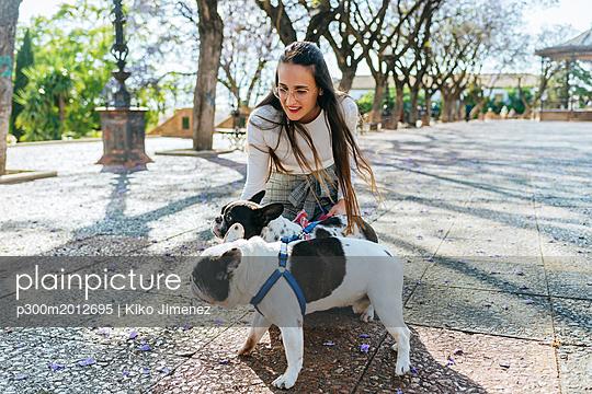 Woman caressing her two dogs - p300m2012695 von Kiko Jimenez