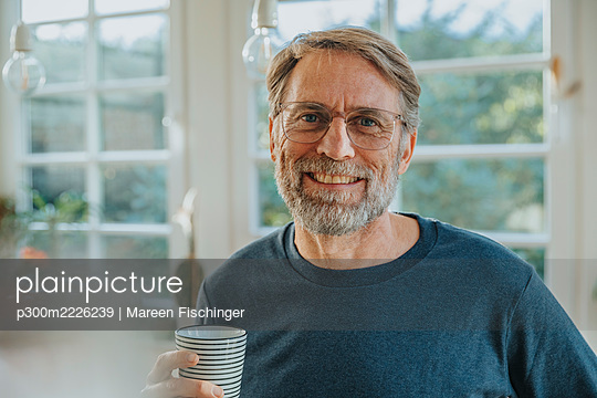 Smiling mature man with tea cup standing at home - p300m2226239 by Mareen Fischinger