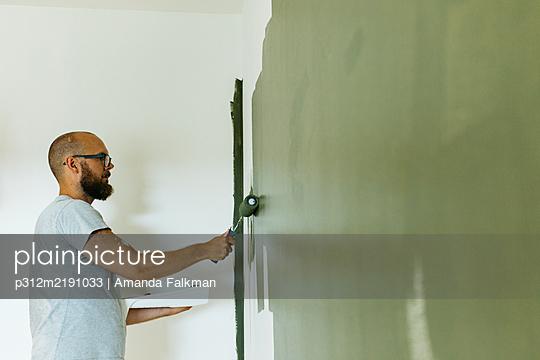 Man painting walls - p312m2191033 by Amanda Falkman