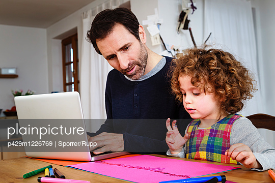 Girl drawing at table while father using laptop - p429m1226769 by Sporrer/Rupp