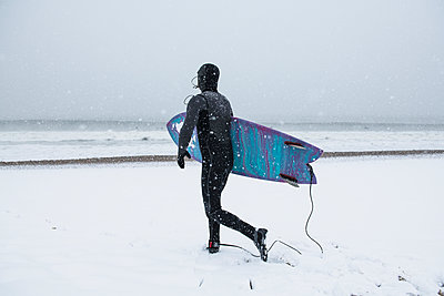 Man preparing to go surfing during winter snow - p1166m2177096 by Cavan Images