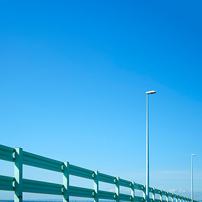 Two street lamps and a railing against a blue sky - p1228m1168786 by Benjamin Harte