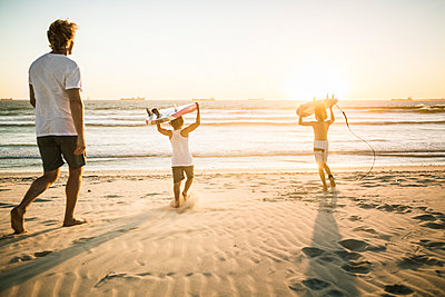 Father and two sons with surfboards walking on the beach at sunset - p300m2167514 by Floco Images