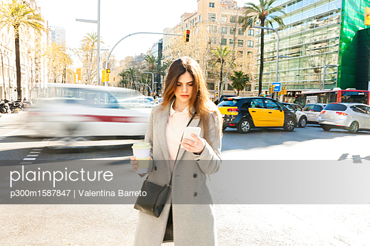 Spain, Barcelona, young woman with coffee to go standing at roadside looking at cell phone - p300m1587847 von Valentina Barreto