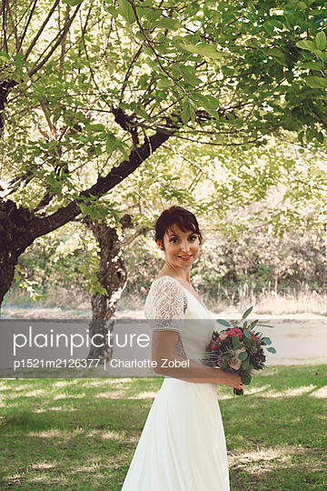 Bride holding a bouquet under the trees - p1521m2126377 by Charlotte Zobel