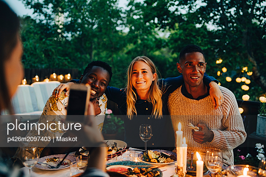 Woman photographing happy male and female friends sitting at table during dinner party - p426m2097403 by Maskot