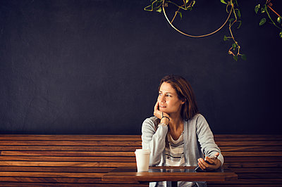 Thoughtful woman looking away while sitting at cafe table - p1166m1140310 by Cavan Images