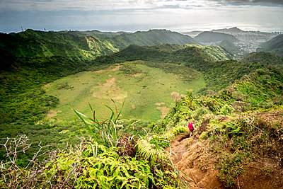 A woman with a backpack hikes along the Ka'au Crater Trail - p1166m2090644 by Cavan Images