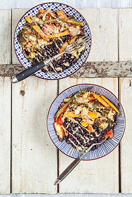 Vegan Buddha bowl of black rice, roasted vegetables, Tahini sauce and sesame seeds - p300m1228187 by Susan Brooks-Dammann