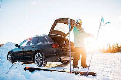 Man by a car with skiing equipment in Osterdalen, Norway - p352m1523658 by Benjamin Rudström