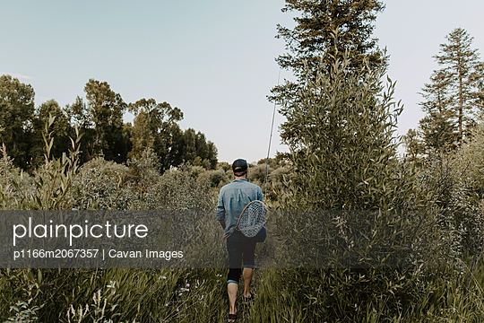 Rear view of man with fishing equipment walking amidst plants against clear sky in forest - p1166m2067357 by Cavan Images