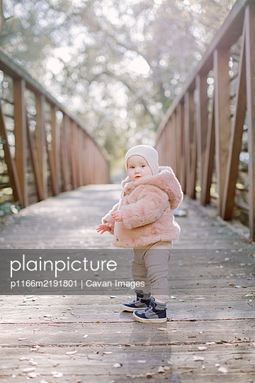 Baby standing on a bridge and looking at camera - p1166m2191801 by Cavan Images
