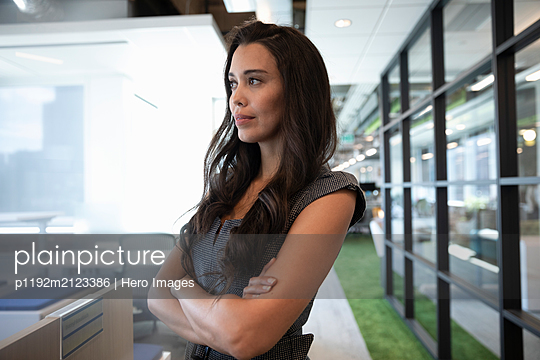 Portrait of businesswoman looking away with arms folded - p1192m2123386 by Hero Images